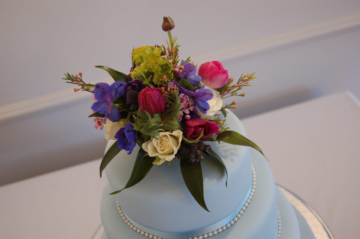 Rich shades of violet, pink and ivory anenomes, wax flowers, spray roses, delphiniums and burplurum.